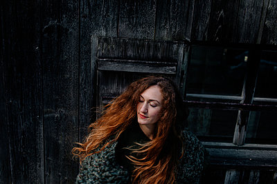 Portrait of redheaded woman with closed eyes, wooden wall in the background - p300m2132387 by Oxana Guryanova
