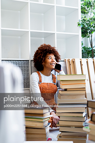 Afro woman on phone call surrounded by stack of books while moving in new apartment - p300m2251594 by Giorgio Fochesato