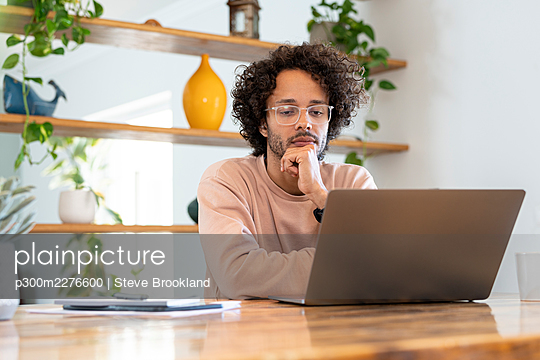 Young businessman wearing eyeglasses while using laptop on table at home - p300m2276600 by Steve Brookland