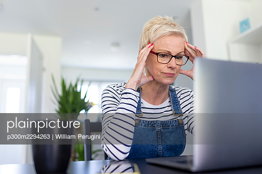 Frustrated female professional looking at laptop in home office - p300m2294263 by William Perugini
