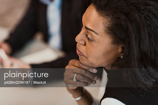 High angle view of businesswoman with hand on chin in corporate training - p426m2296187 by Maskot