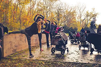 Frauen mit Kinderwagen machen Gymnastik im Park - p299m1502640 von Silke Heyer
