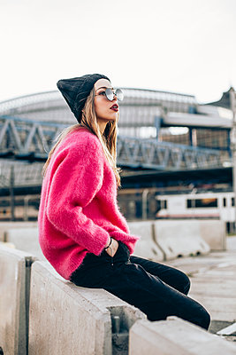 Portrait of fashionable young woman wearing sunglasses, cap and pink knit pullover - p300m2078762 by Aitor Carrera Porté