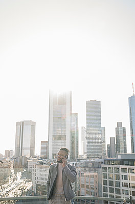 Stylish man on the phone on observation terrace with skycraper view, Frankfurt, Germany - p300m2180016 by Hernandez and Sorokina