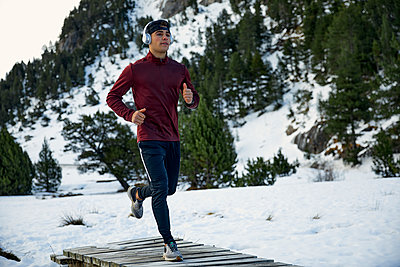 Determined young male athlete running on footbridge while listening music during winter - p300m2250036 by Aitor Carrera Porté