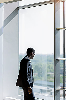 Businessman looking through window in office - p300m2281501 by Buero Monaco