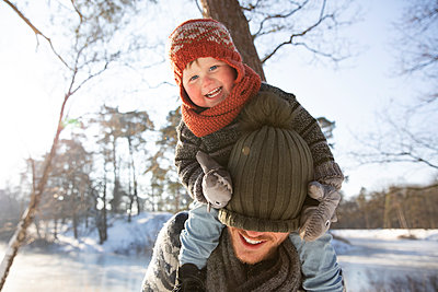 Smiling son pulling knit hat over father's face during winter - p300m2281794 by Frank van Delft