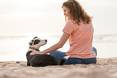Smiling young woman stroking Jack Russell Terrier while sitting at beach - p300m2286964 by Steve Brookland