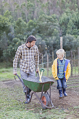 Father and son pushing wheelbarrow - p42915787f by Hybrid Images