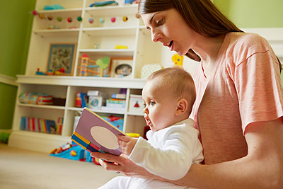 Mid adult woman and baby daughter reading storybook in playroom - p429m1408045 by Emma Kim