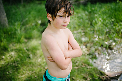 Canada, Ontario, Shirtless boy standing wet after swimming outdoors - p924m2271307 by Liz Cooper