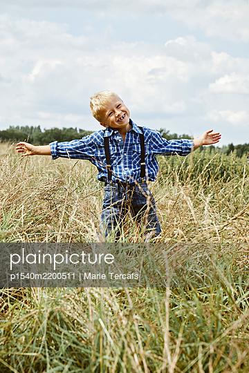 portrait of a boy in a meadow - p1540m2200511 by Marie Tercafs