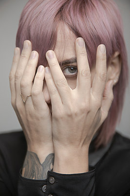 Portrait beautiful non-gender person with pink hair hiding head in hands - p1192m2066239 by Hero Images
