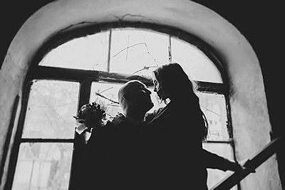 Newlywed couple embracing in window - p1427m2200180 by Kateryna Soroka