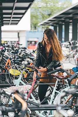 Young woman with bicycle using cell phone in the city - p300m2005531 von Kniel Synnatzschke