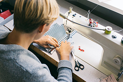 Woman using sewing machine on table in studio - p300m2070492 by Visualspectrum
