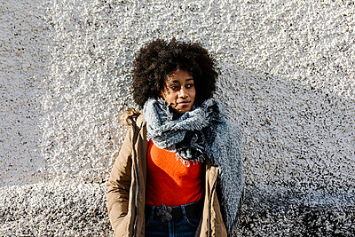 Afro young woman with hands in pockets against textured wall - p300m2256855 by Xavier Lorenzo