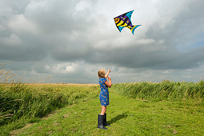 Girl flying kite in rural field - p429m711769f by Mischa Keijser