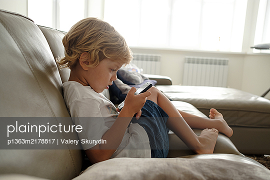 Boy is playing with smartphone at home, stay at home due to Covid-19 - p1363m2178817 by Valery Skurydin