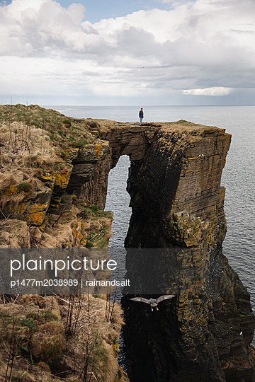 Man at Scottish cliff - p1477m2038989 by rainandsalt