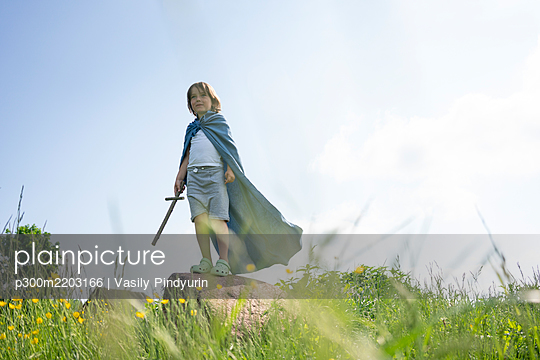 Playful boy wearing cape standing on rock against sky during sunny day - p300m2203166 by Vasily Pindyurin