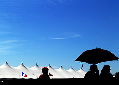 Silhouetted figures by events marquee - p1072m828937 by Clive Branson