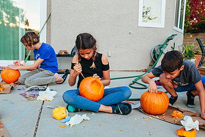 Boy looks into pumpkin while sisters continue to carve theirs - p1166m2078356 by Cavan Images