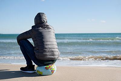 Man sitting in  a world globe on a beach - p1423m1516412 by JUAN MOYANO