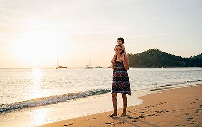 Thailand, Krabi, Koh Lanta, Mother with little daughter on her shoulders on the beach at sunset - p300m2004114 von Gemma Ferrando