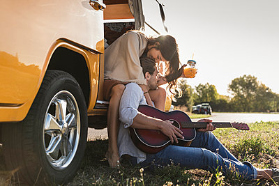 Affectionate couple on a road trip, taking a break, kissing, playing guitar - p300m2070755 by Uwe Umstätter