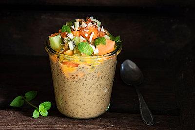 Jar of vegan pudding with chia, almond milk, persimmon, kiwi fruit, papaya, passion fruit and almonds - p300m2155939 by Eva Gruendemann