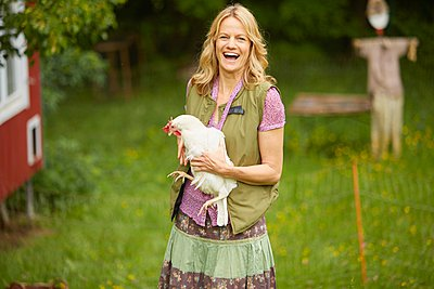 Portrait of woman in field holding white hen - p429m1047246 by Stephen Lux