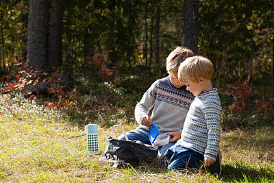 Brothers having picnic in forest on sunny day - p429m2145496 by Tiina & Geir