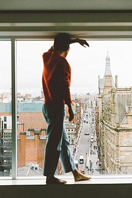 Frau steht nachdenklich am Fenster - p432m2087093 von mia takahara