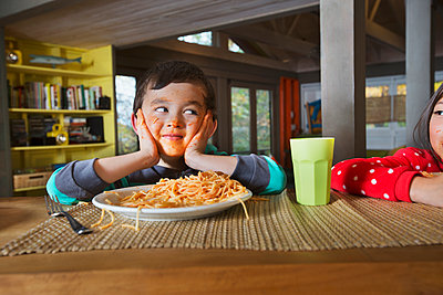 Sister watching Mixed Race brother with messy face eating spaghetti - p555m1231761 by Jasper Cole