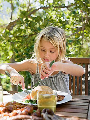 Girl eating meal, outdoors - p9243290f by Image Source