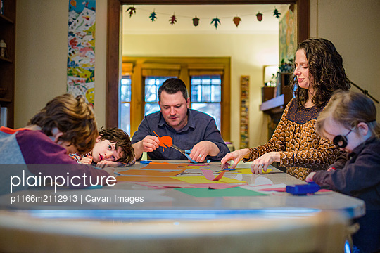 A family sit together at a dining room table creating paper craft art - p1166m2112913 by Cavan Images