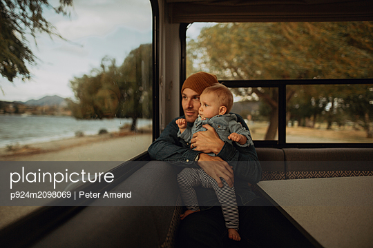 Father and baby looking out window of motorhome, Wanaka, Taranaki, New Zealand - p924m2098069 by Peter Amend