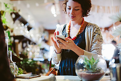 Cropped image of owner with customer using mobile phone for payment in plant shop - p1166m1422906 by Cavan Images