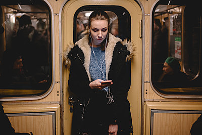 Young woman listening music on phone while traveling in subway train - p1166m2138107 by Cavan Images