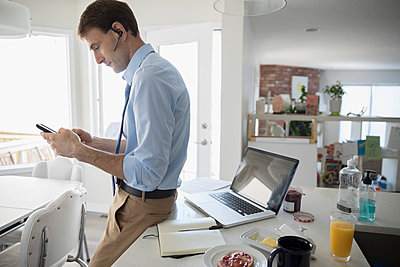 Businessman working at laptop in morning breakfast kitchen - p1192m1490771 by Hero Images