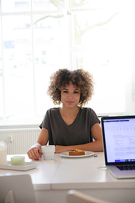 Smiling young woman sitting at table at home with coffee and cake - p300m1535315 by harry + lidy