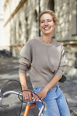 Portrait of happy woman with bicycle in the city - p300m2104392 by Philipp Nemenz