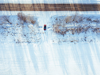 Russia, Moscow Oblast, Aerial view of car driving into snow-covered field - p300m2166785 by Konstantin Trubavin