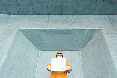 Portrait of man wearing protective clothing holding a blank sign - p300m2170894 by Valentin Weinhäupl