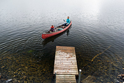 Mother and young son push away from dock at Kezar Lake - p343m1167895 by Monica Donovan