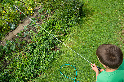 Boy with garden hose - p427m917894 by Ralf Mohr