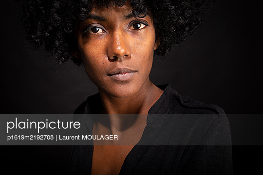 Studio portrait of a young black gril with curly hair - p1619m2192708 by Laurent MOULAGER