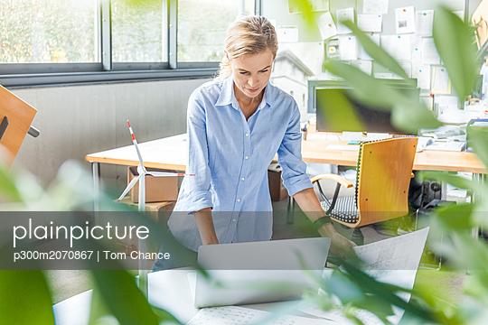plainpicture - plainpicture p300m2070867 - Woman in office with plan, ... - DEEPOL by plainpicture/Tom Chance