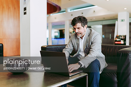 Male entrepreneur using laptop while sitting at lobby in hotel - p300m2240071 by Daniel González